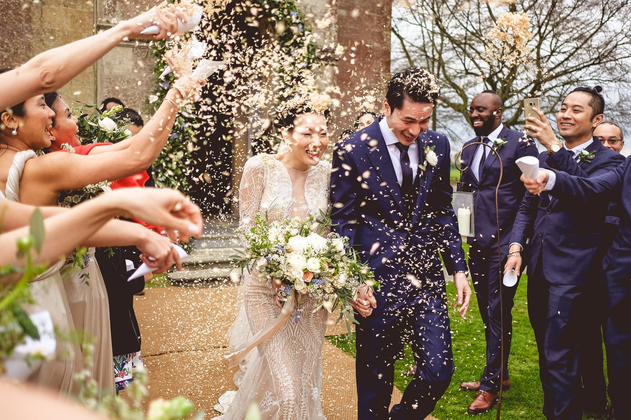 Bride and groom and confetti at a Babington House wedding in Somerset
