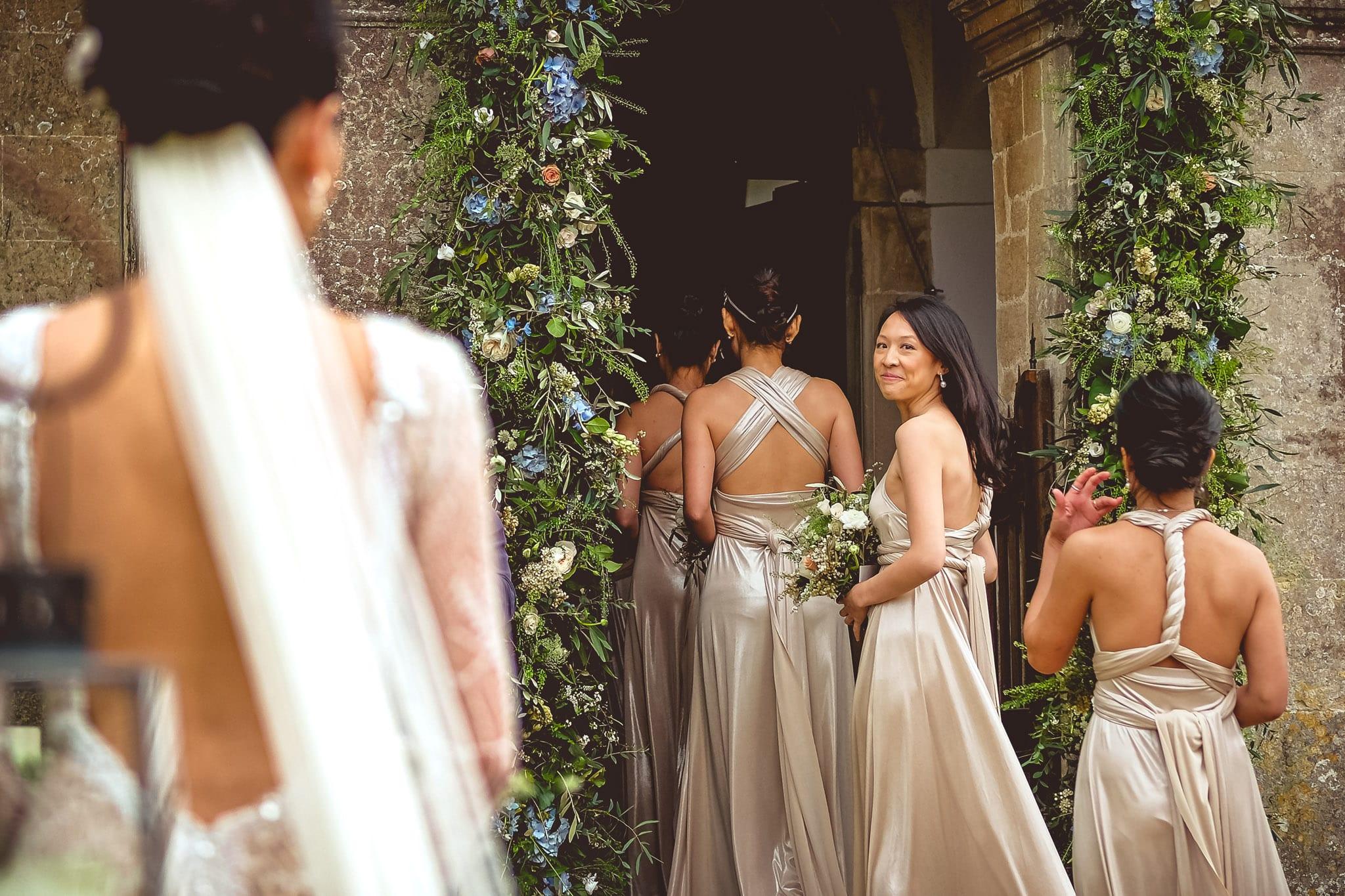 Bride and bridesmaids waiting to enter the church at a Babington House wedding in Somerset