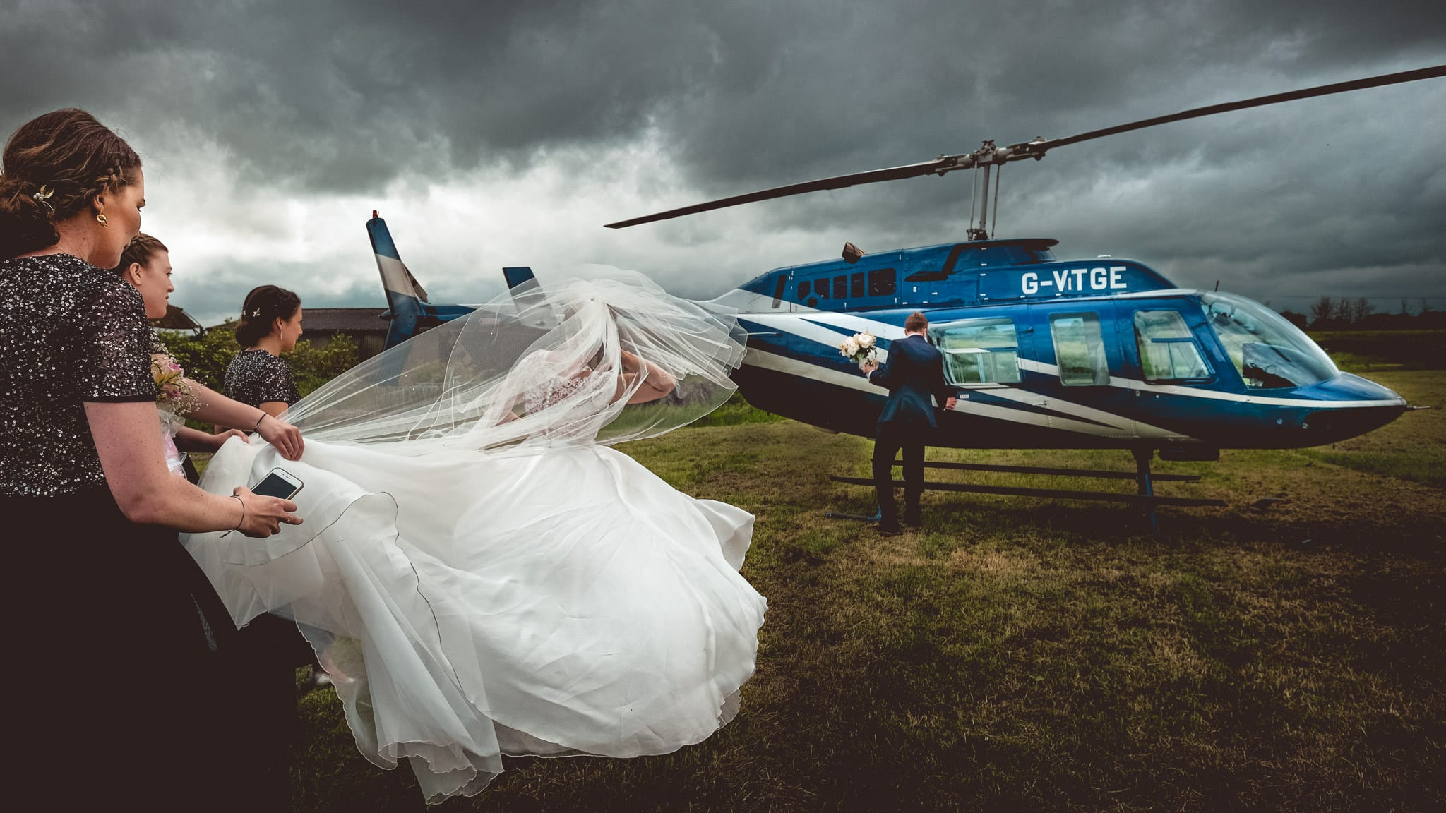 Bride and groom head for the helicopter at an Orchardleigh House wedding in Somerset
