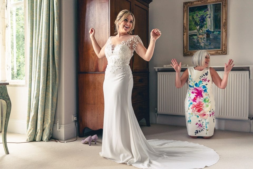 Bride getting into her dress at a Matara Centre wedding in Gloucestershire