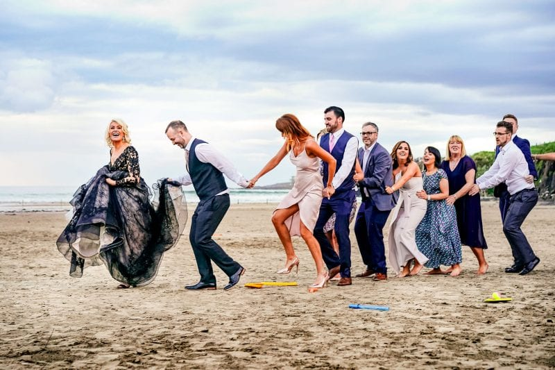 Bride, groom and guests dancing on the beach at a wedding at Harry's Shack in Portstewart Northern Ireland