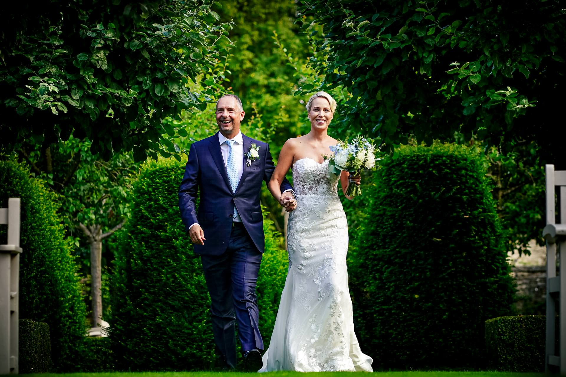 Bride and groom walk into the garden ceremony at a Temple Guiting Barns Wedding in Gloucestershire