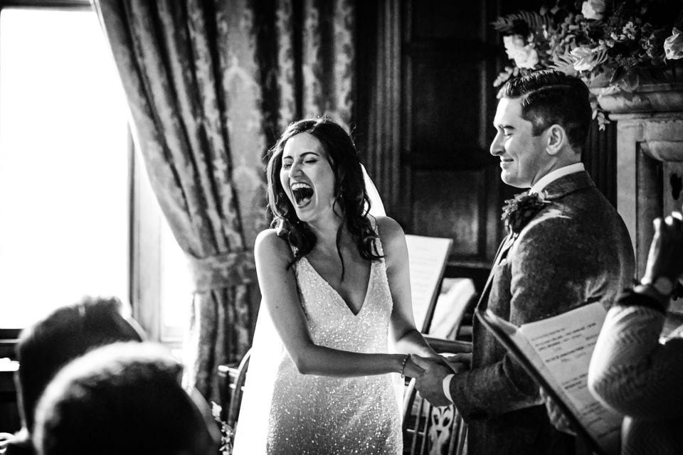 Bride laughing during the ceremony at a Huntsham Court wedding