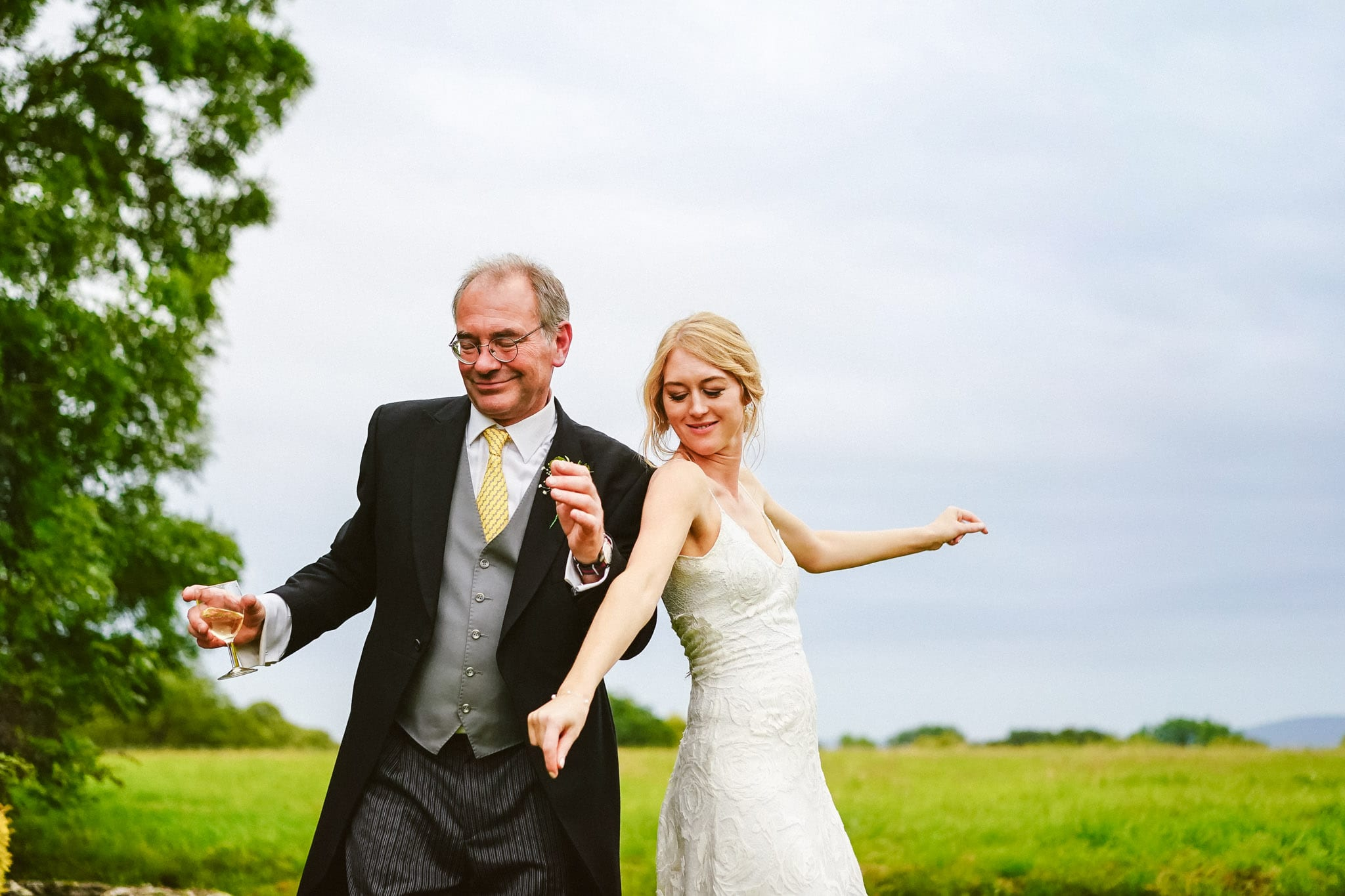 Buckinghamshire wedding photographer and Bride and father dancing outside at a Long Crendon wedding in Buckinghamshire