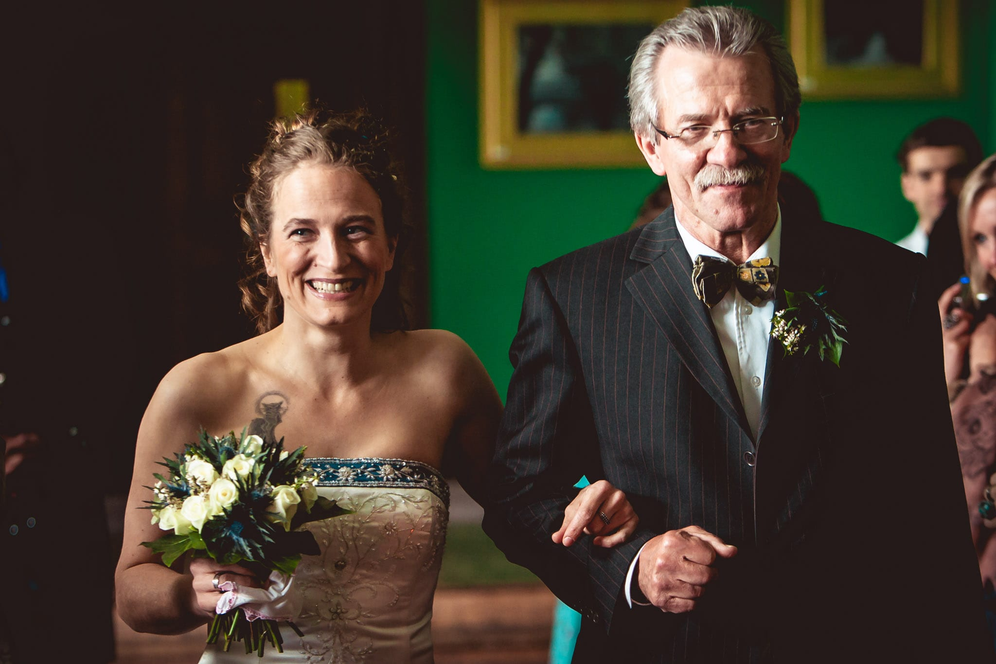 Bride and father walking down the aisle at a Carbisdale Castle wedding in Scotland