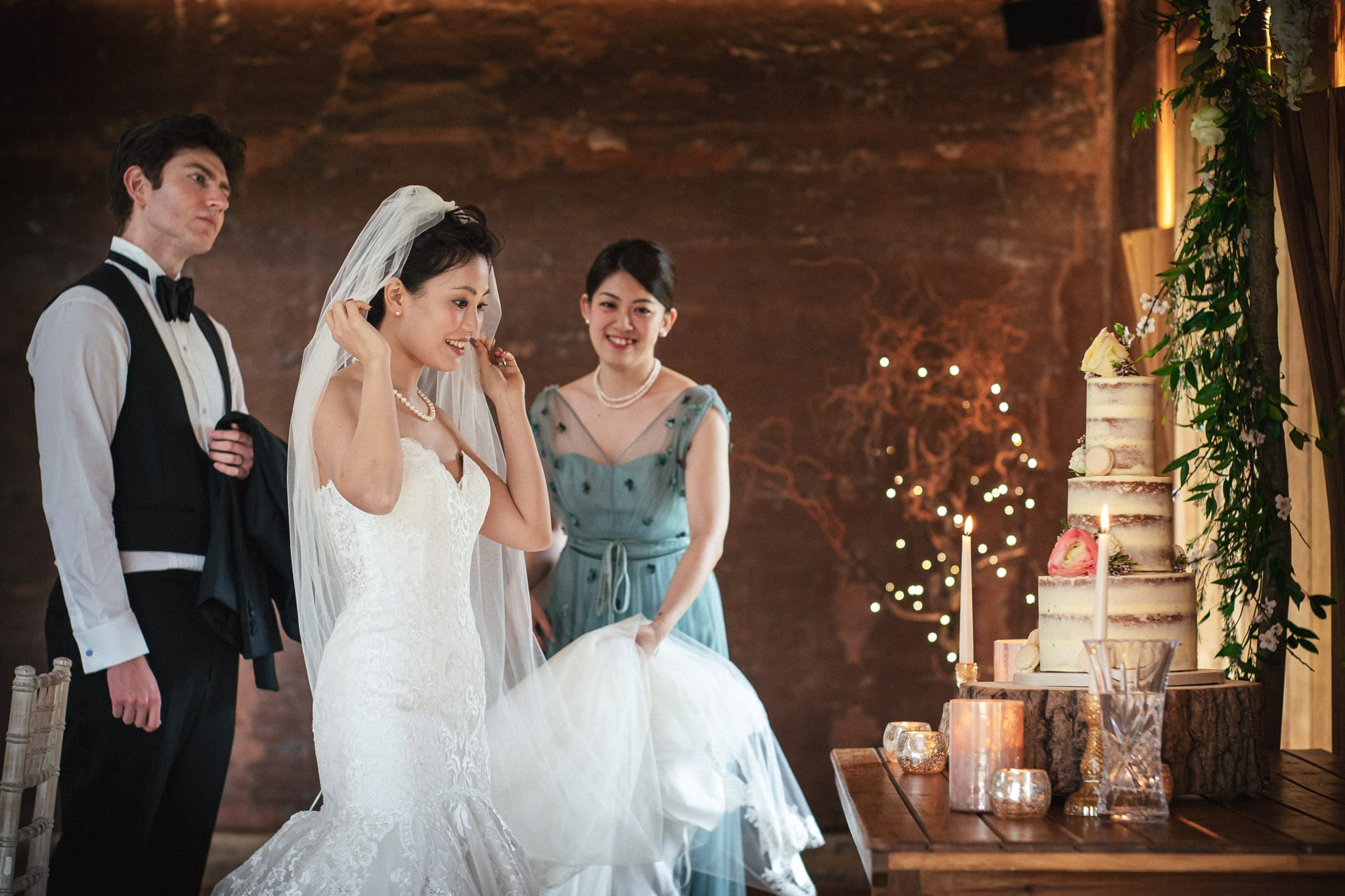 Bride looking at wedding cake at an Elmore Court wedding in Gloucestershire