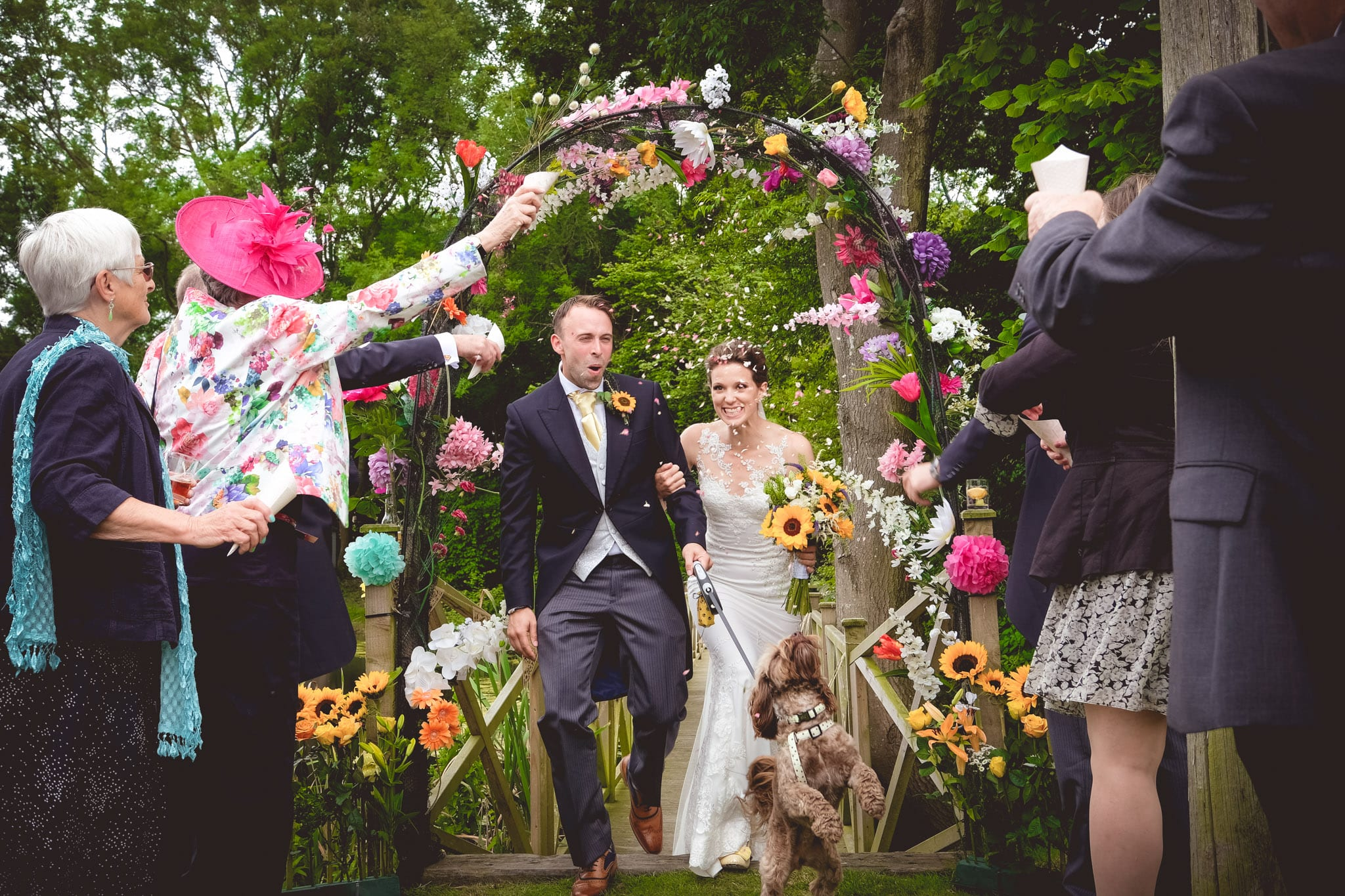 Bride and groom and dog and confetti through a flower arch