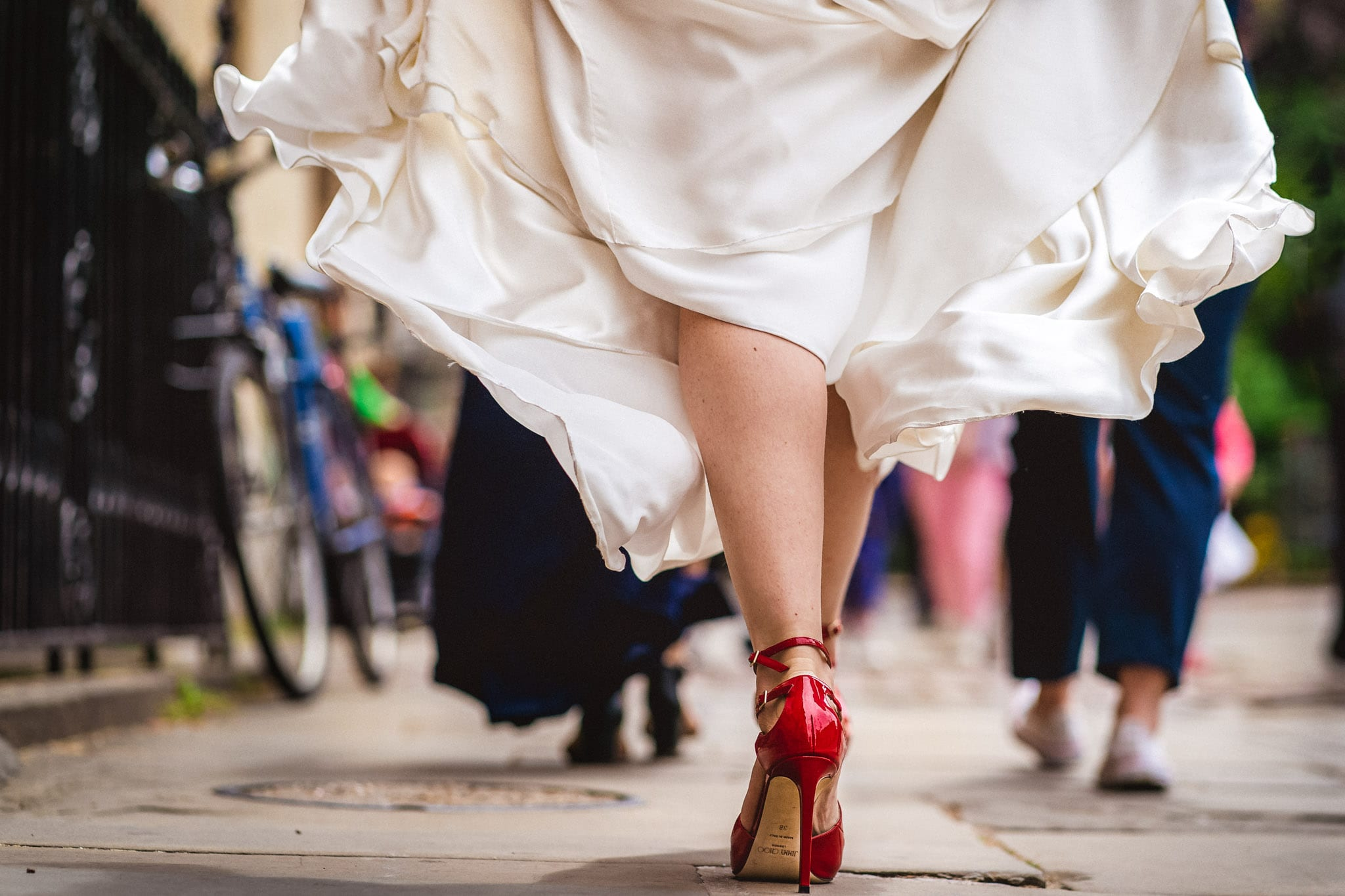 Bride in red Jimmy Choo shoes walking to her Oxford wedding venue