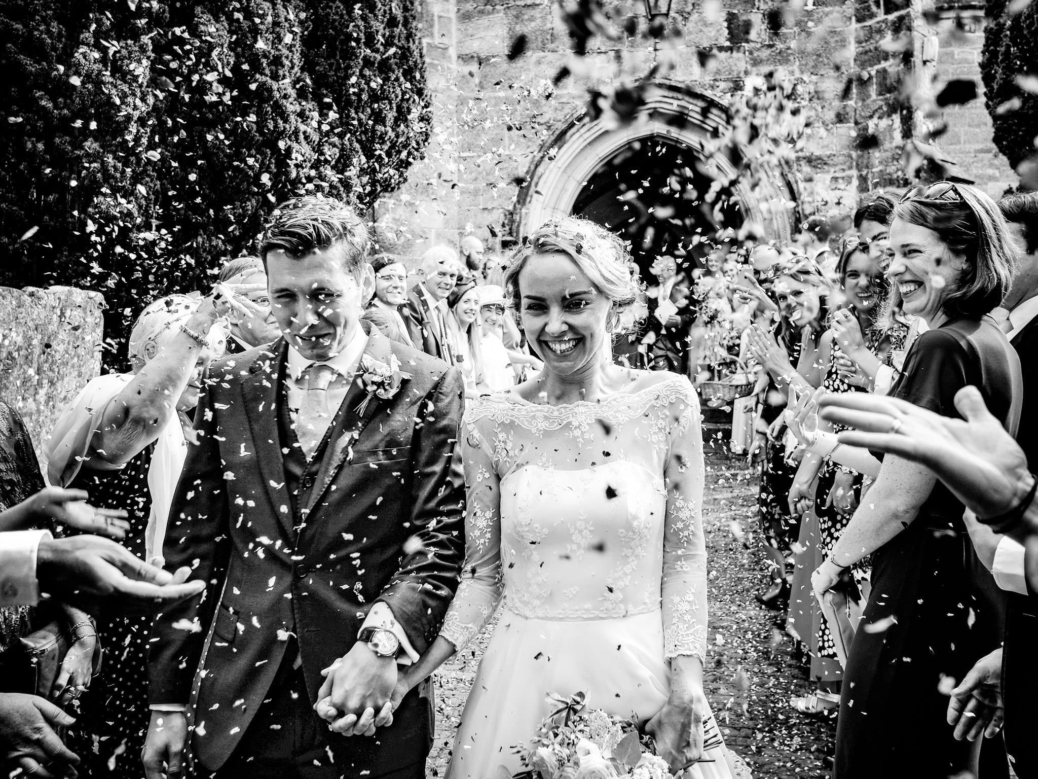 Bride and groom in confetti in black and white